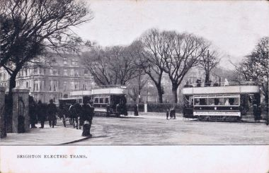 Trams passing the bottom of Victoria Gardens. The Victoria statue is behind the tram on the right.