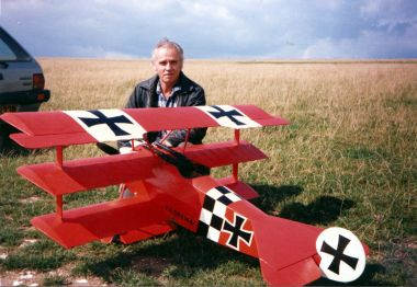 Denis Hefford in a field with his radio-controlled Fokker triplane model