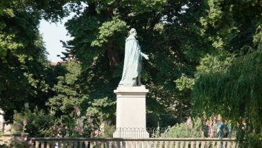 Side view of the statue, looking North from Pavilion Gardens, with Victoria Gardens in the background (on the far side of a road)