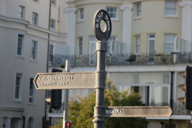 "Kemp Town signage on the seafront, East: ""St James Street Shopping Area"", West: ""Marina"""