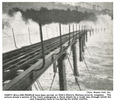 """FORTY MILLION PEOPLE have been carried on Volk's Electric Railway since its inception. The picture shows a section of the track undergoing a fierce attack by a rough sea, through which the cars frequently have to run during the winter months."""