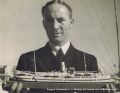 Surgeon Commander EJ Littledale, with his model of hospital ship RFA Maine.jpg