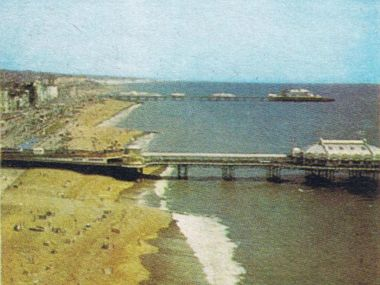 1965: Photograph of the West Pier (foreground) and Palace Pier (background), aerial view looking East